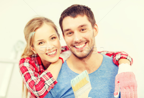 smiling couple covered with paint with paint brush Stock photo © dolgachov