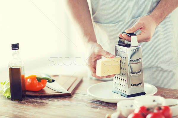 Stock photo: close up of male hands grating cheese