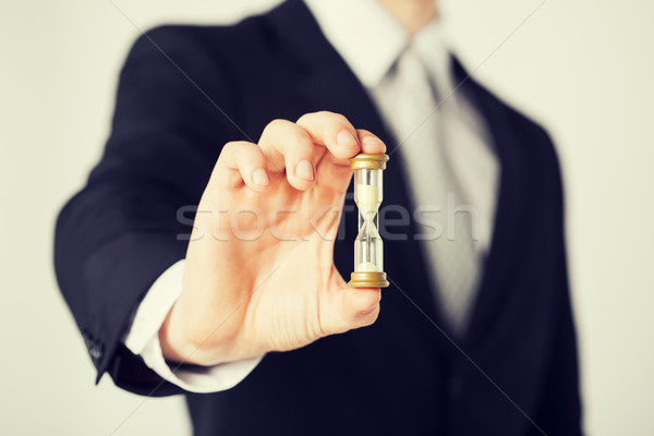 man hand holding hourglass Stock photo © dolgachov