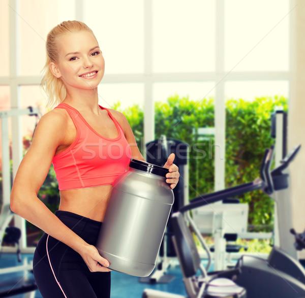 Sonriendo deportivo mujer jar proteína fitness Foto stock © dolgachov