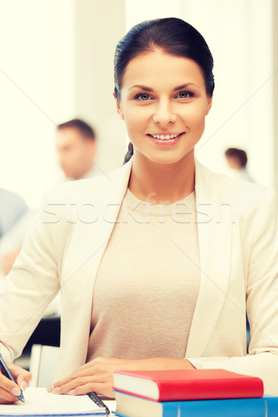 attractive businesswoman taking notes in office Stock photo © dolgachov