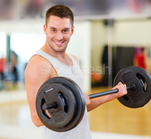 smiling man with barbell in gym Stock photo © dolgachov