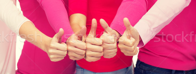 close up of women in pink shirts showing thumbs up Stock photo © dolgachov