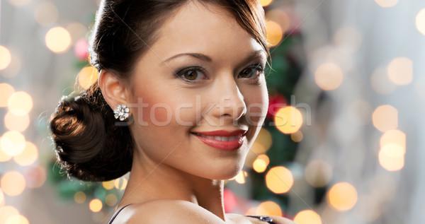 woman with diamond earring over christmas lights Stock photo © dolgachov