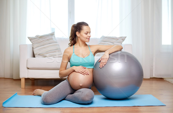 Stock photo: happy pregnant woman with fitball at home
