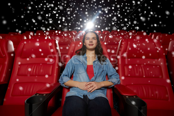 young woman watching movie in theater stock photo syda productions