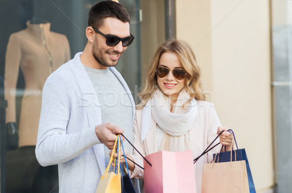 happy couple with shopping bags at shop window Stock photo © dolgachov