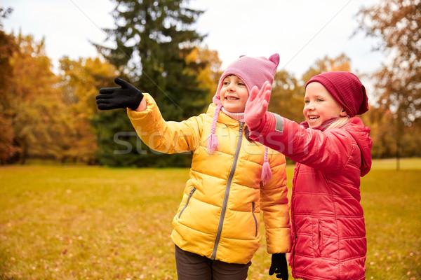 two happy little girls waving hand in autumn park Stock photo © dolgachov