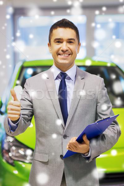 man showing thumbs up at auto show or car salon Stock photo © dolgachov