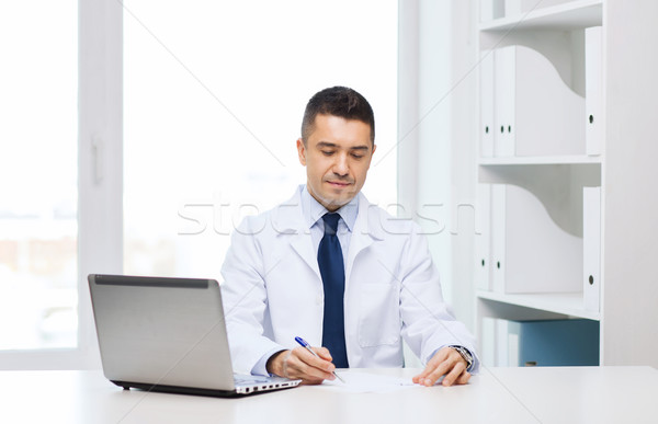 smiling male doctor with laptop in medical office Stock photo © dolgachov