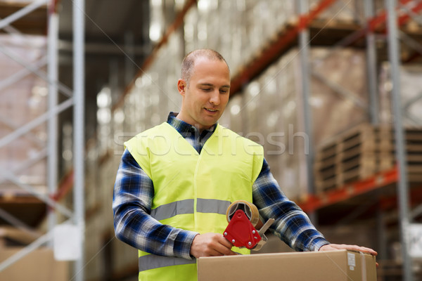 man in safety vest packing box at warehouse Stock photo © dolgachov