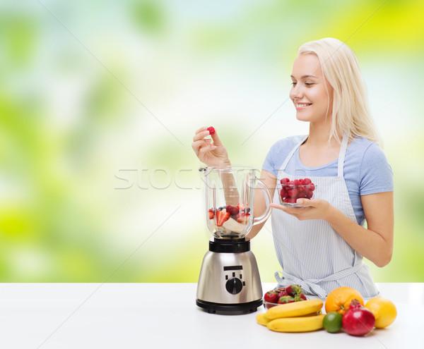 Stock photo: smiling woman with blender preparing shake at home