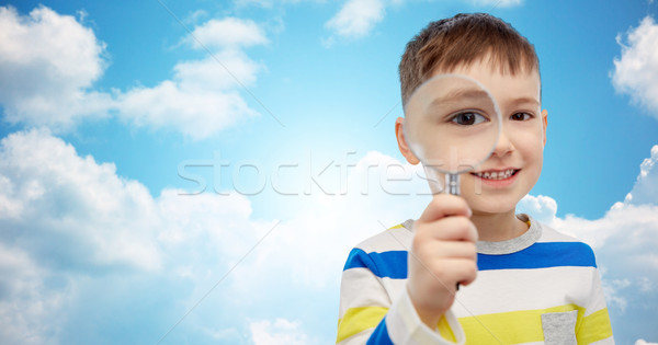 Stock photo: happy little boy looking through magnifying glass