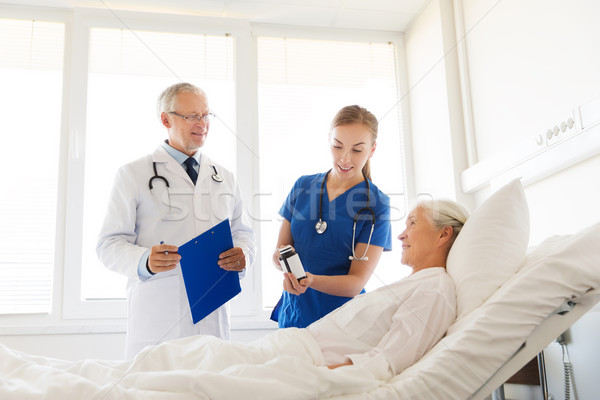 Stock photo: doctor giving medicine to senior woman at hospital