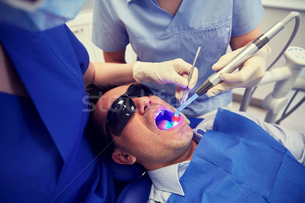 dentists treating male patient teeth at clinic Stock photo © dolgachov
