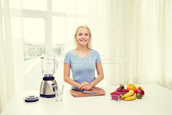 smiling woman with blender and fruits at home Stock photo © dolgachov