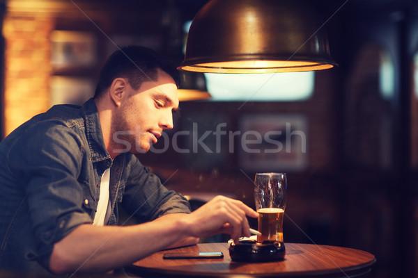 Adam içme bira sigara içme sigara bar Stok fotoğraf © dolgachov