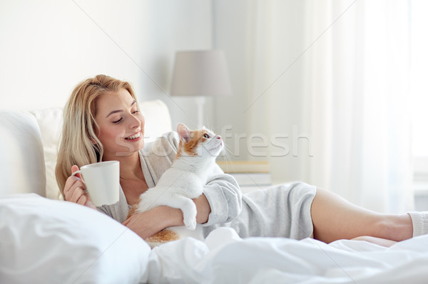 happy woman with coffee and cat in bed at home Stock photo © dolgachov