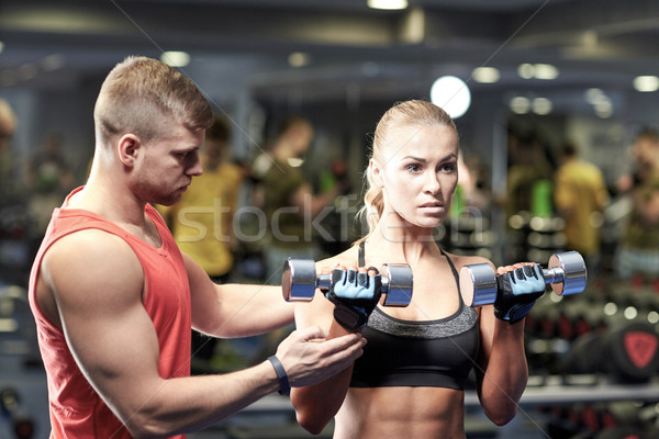 young couple with dumbbells flexing muscles in gym Stock photo © dolgachov
