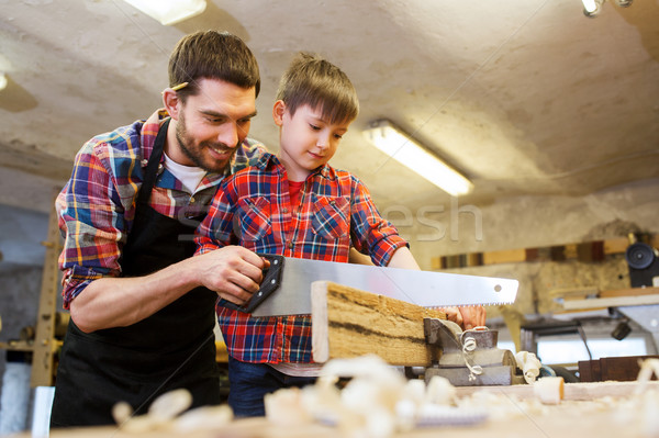 Stock photo: father and son with saw working at workshop