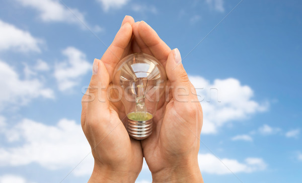 Stock photo: close up of hands holding edison lamp or lightbulb