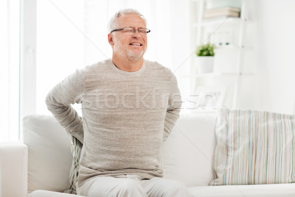 unhappy senior man suffering from backache at home Stock photo © dolgachov