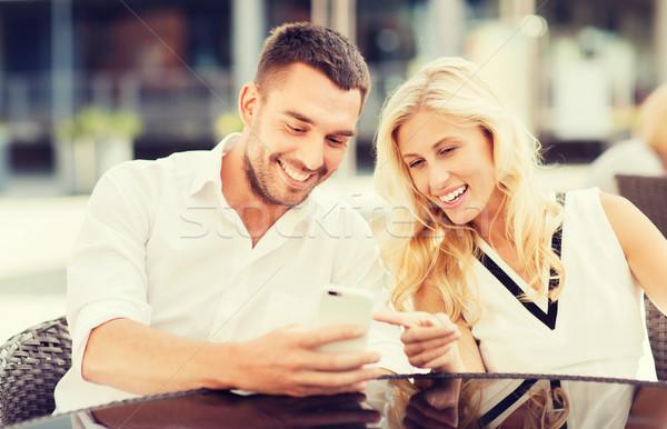 happy couple with smatphone at city street cafe Stock photo © dolgachov