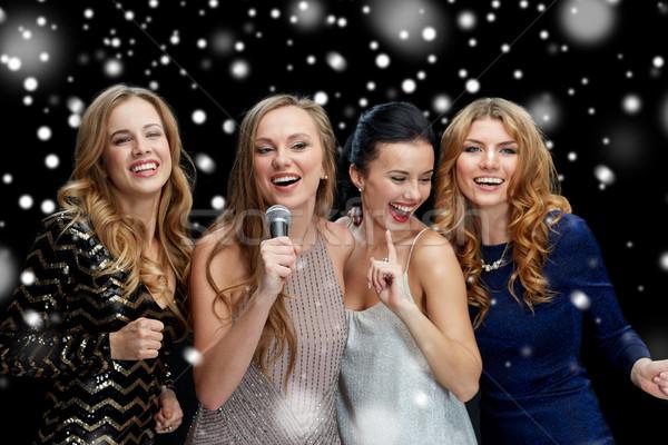 Gelukkig jonge vrouwen microfoon zingen karaoke nieuwjaar Stockfoto © dolgachov