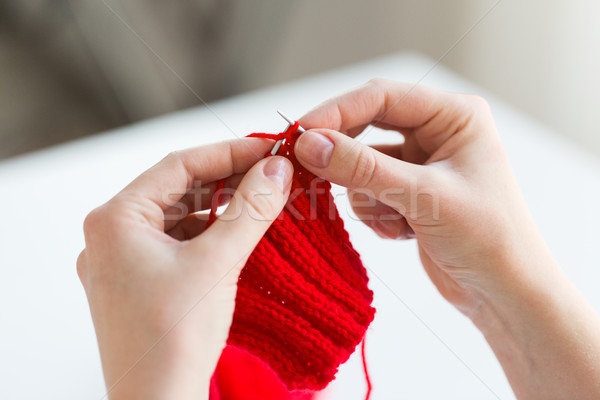 Stock photo: close up of hands knitting with needles and yarn