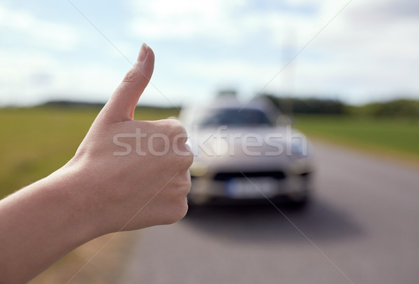 hitchhiker stopping car with thumbs up hand sign Stock photo © dolgachov