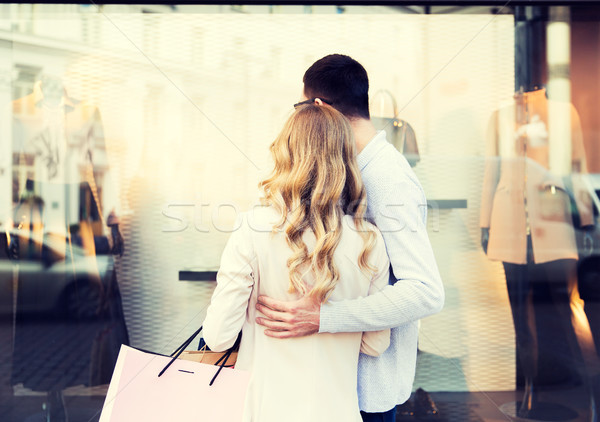 couple with shopping bags looking at shop window Stock photo © dolgachov