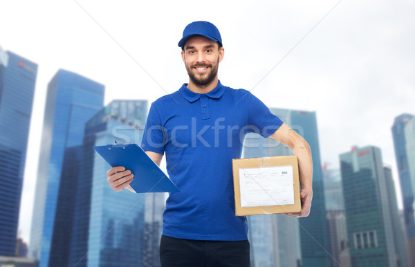 happy delivery man with parcel box and clipboard Stock photo © dolgachov