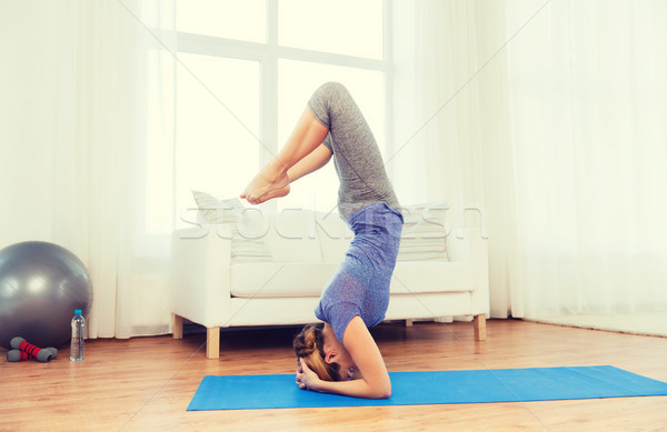 woman making yoga in headstand pose on mat Stock photo © dolgachov