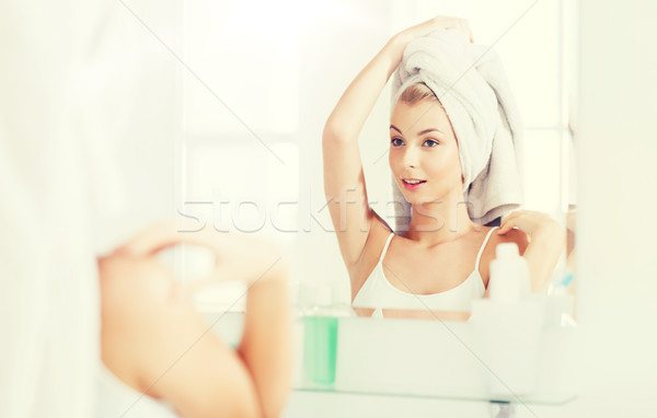 happy young woman with towel at mirror in bathroom Stock photo © dolgachov