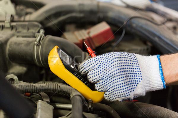 auto mechanic man with multimeter testing battery Stock photo © dolgachov