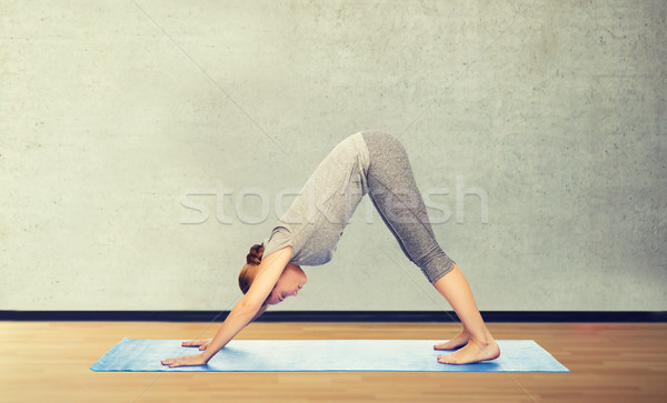 woman making yoga dog pose on mat Stock photo © dolgachov