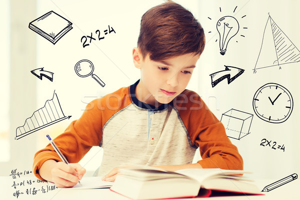 student boy with book writing to notebook at home Stock photo © dolgachov