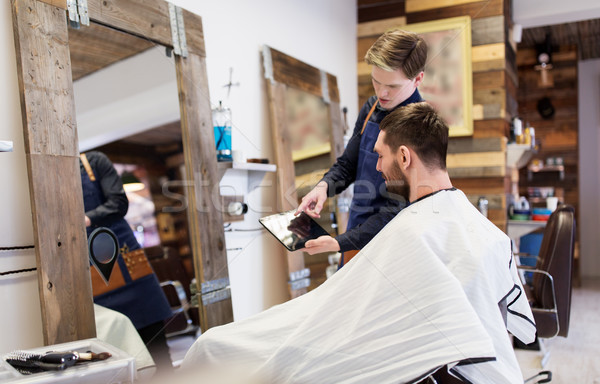 barber showing tablet pc to man at barbershop Stock photo © dolgachov