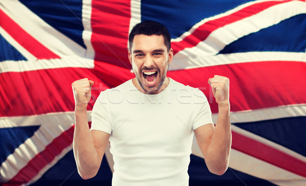 angry man showing fists over brittish flag Stock photo © dolgachov