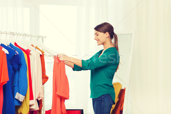 happy woman with shopping bags and clothes at home Stock photo © dolgachov
