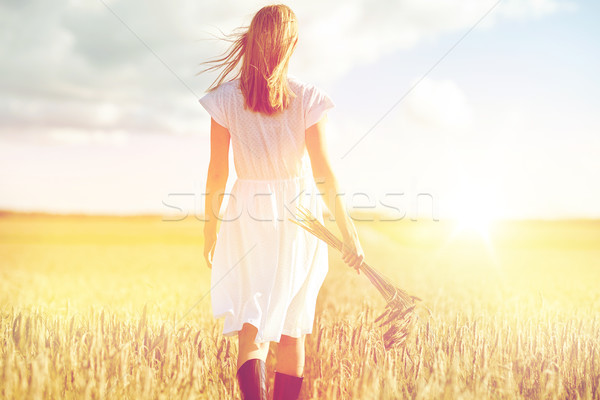 Stock photo: young woman with cereal spikelets walking on field
