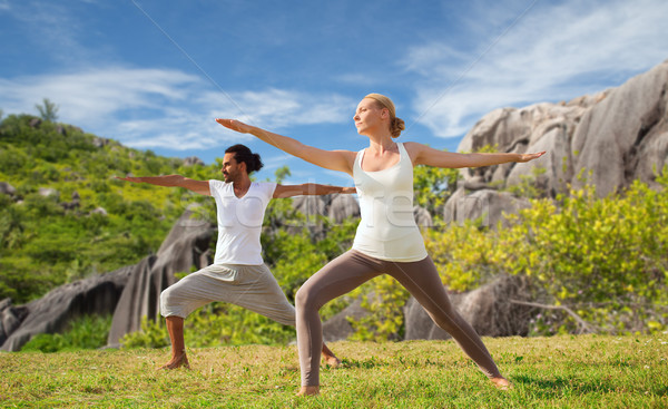 couple making yoga in warrior pose at seaside Stock photo © dolgachov