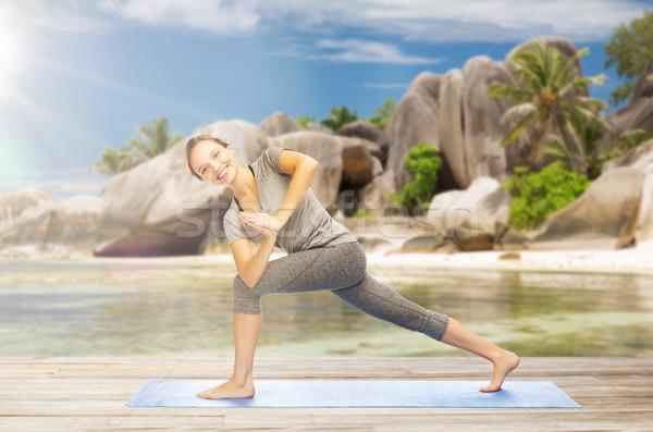 woman doing yoga side angle pose on beach Stock photo © dolgachov