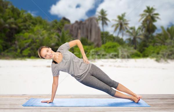 woman doing yoga in side plank pose on beach Stock photo © dolgachov