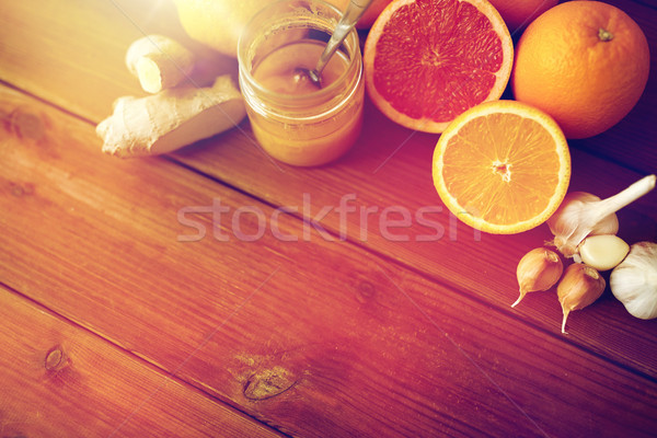 honey, citrus fruits, ginger and garlic on wood Stock photo © dolgachov