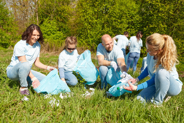 volunteers with garbage bags cleaning park area Stock photo © dolgachov