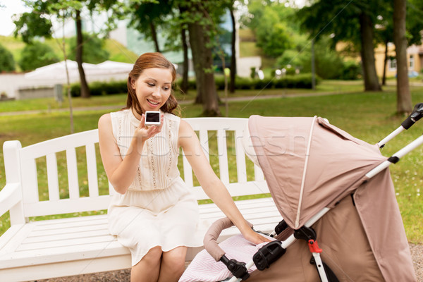 mother with stroller and smartphone at summer park Stock photo © dolgachov