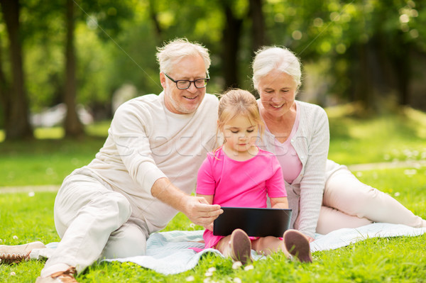 grandparents and granddaughter with tablet pc Stock photo © dolgachov