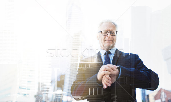 senior businessman checking time on his wristwatch Stock photo © dolgachov