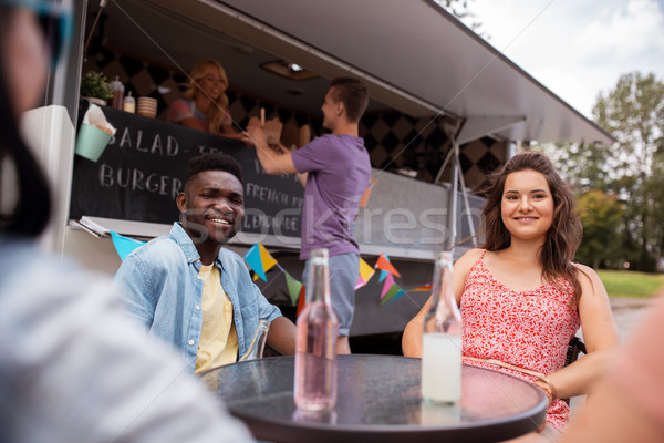 friends with drinks sitting at table at food truck Stock photo © dolgachov